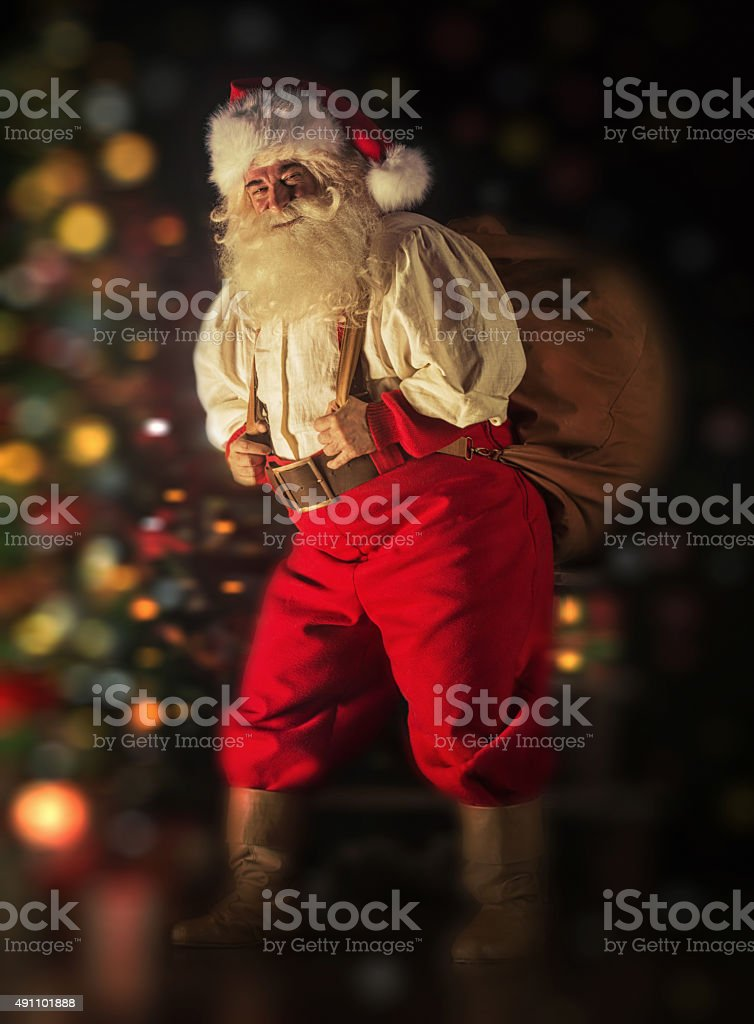 Santa Claus carrying huge sack with presents stock photo