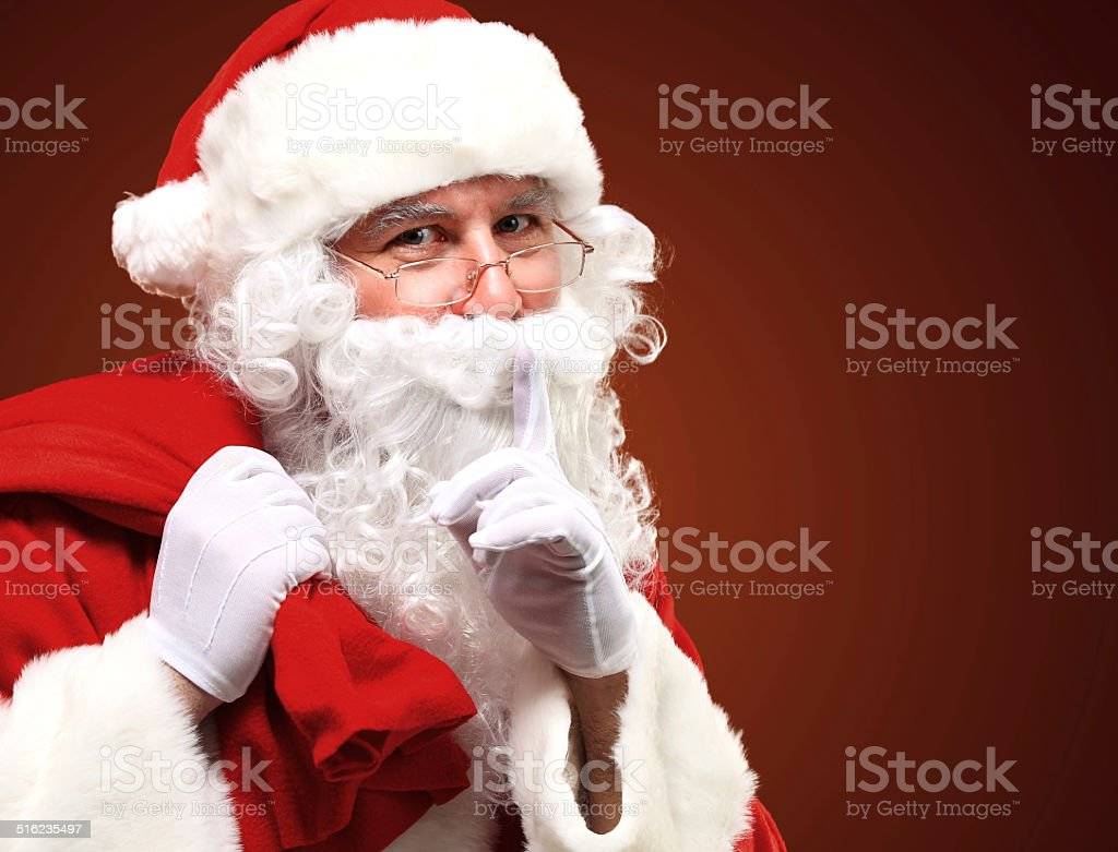 Santa Claus carrying red sack and showing gesture of silence stock photo