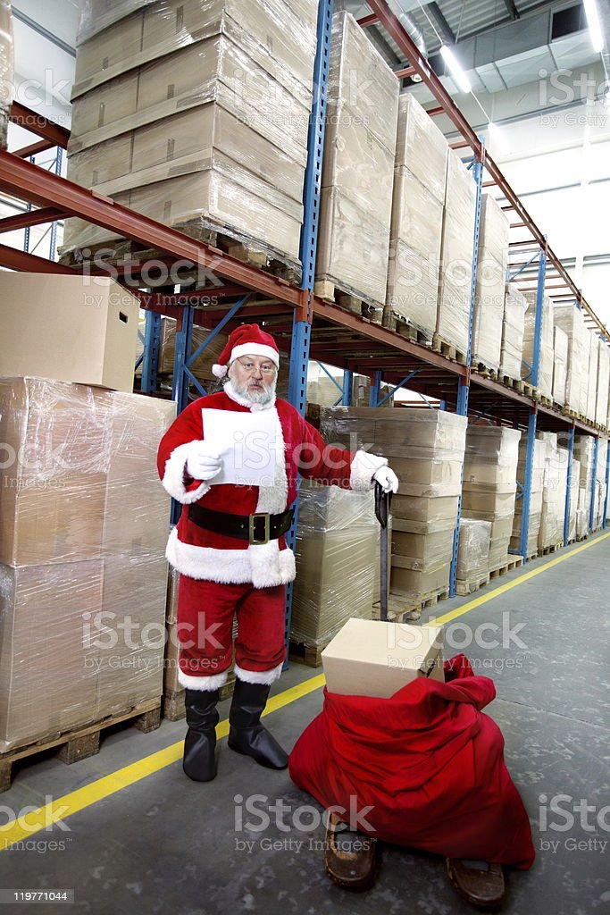 Santa claus checking list of presents in storehouse royalty-free stock photo