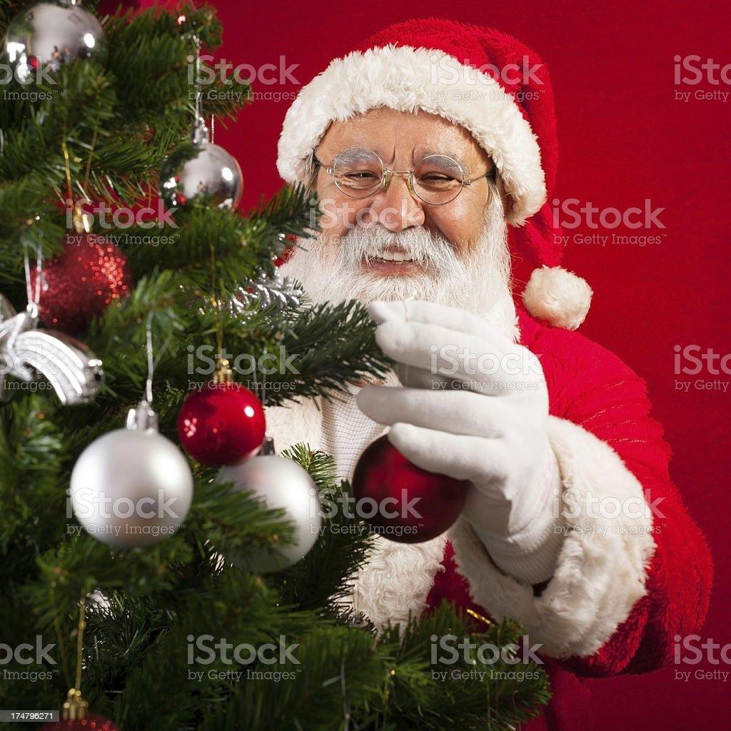 Santa Claus decorates a Christmas tree royalty-free stock photo