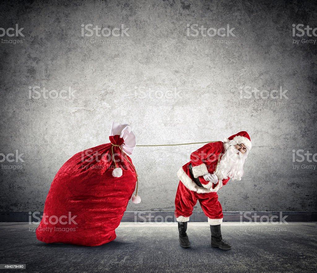 Santa Claus Dragging A Big Sack of Presents stock photo