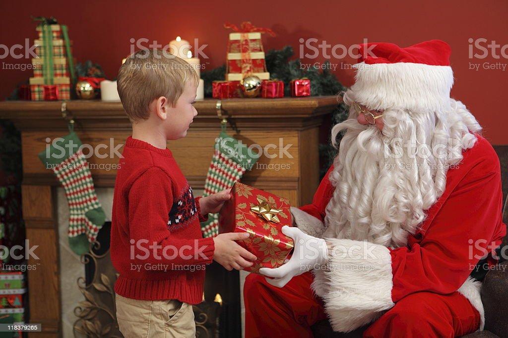 Santa Claus gives young boy Christmas gift royalty-free stock photo