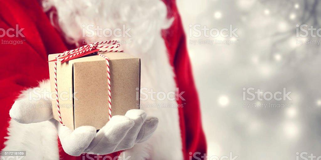 Santa Claus giving a gift stock photo