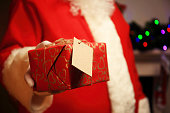 Santa Claus gloved hands holding giftbox