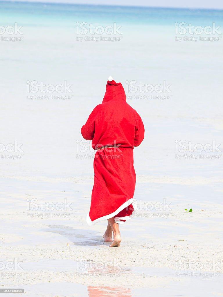 Santa Claus going away into the Ocean on beach, India stock photo