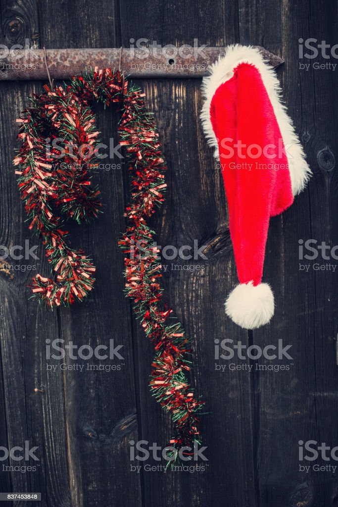 Santa Claus hat and christmas chain hanging on the old wooden door. stock photo