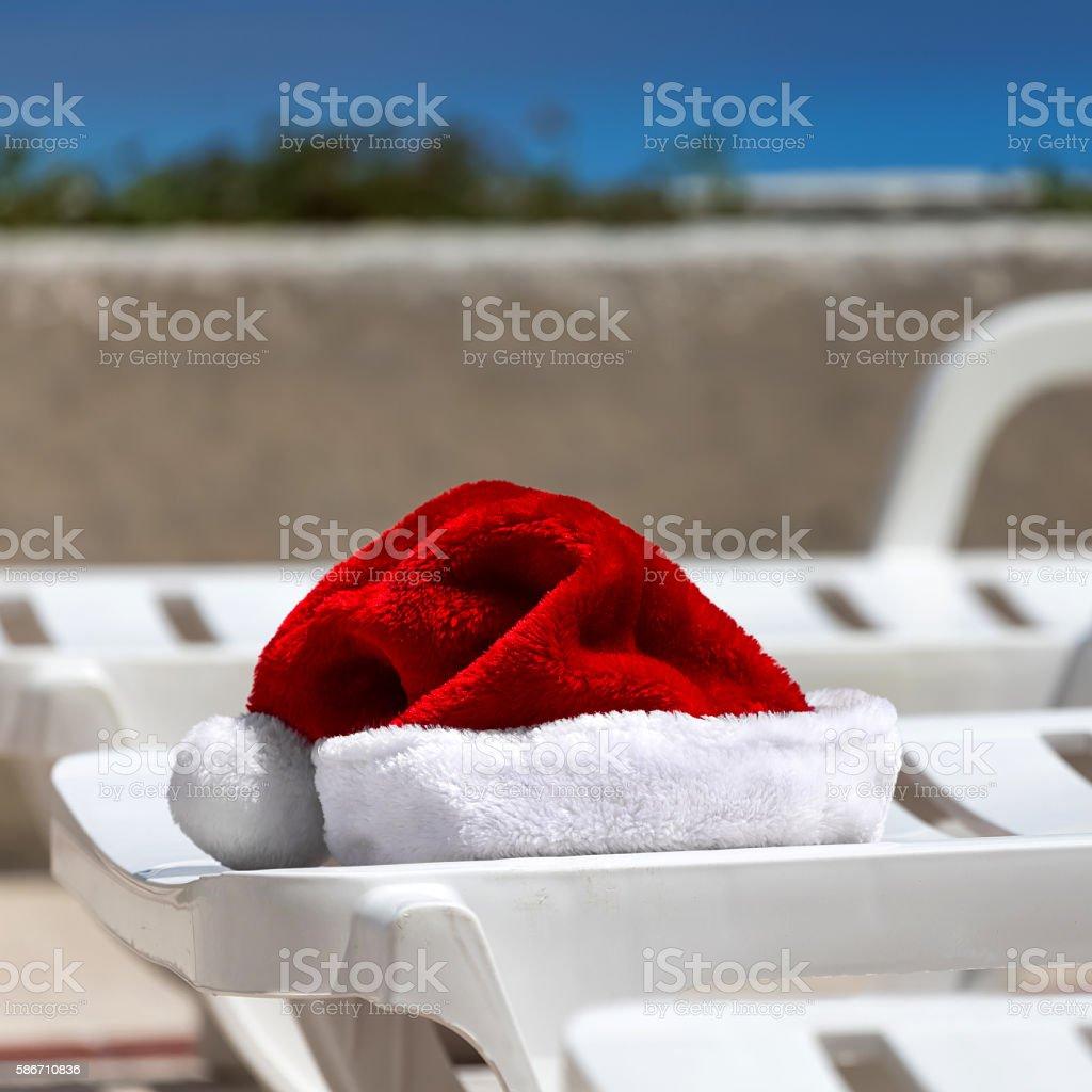 Santa Claus Hat on sunbed near swimming pool stock photo