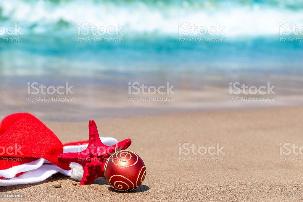 Santa Claus hat on the sand near the sea stock photo