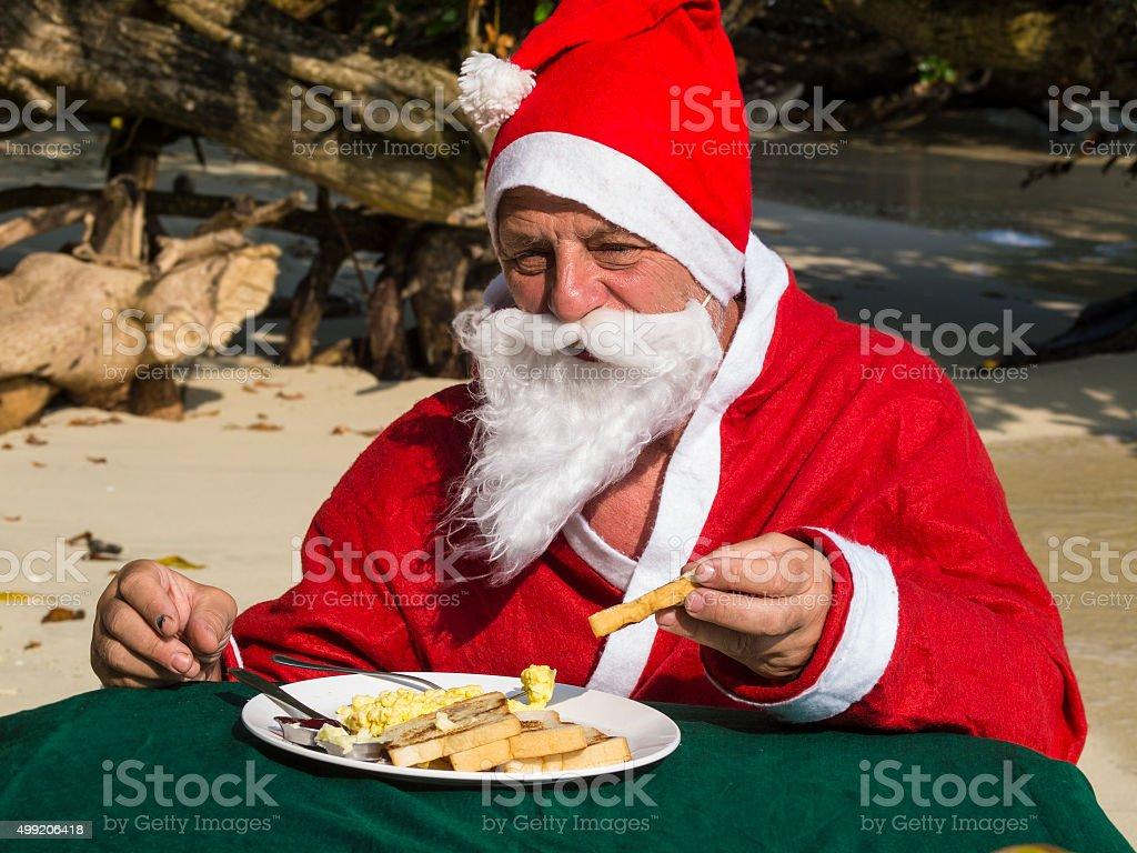 Santa Claus having egg for Breakfast in nature stock photo
