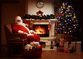 Santa Claus having rest in chair near  fireplace at home