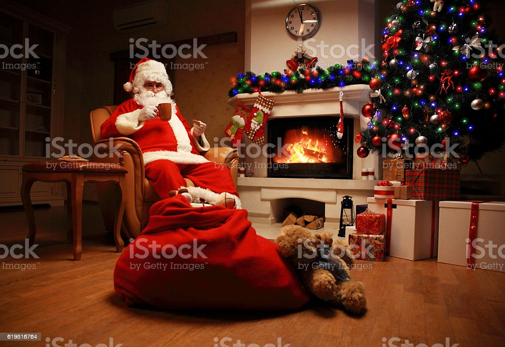 Santa Claus having rest in chair near  fireplace at home stock photo