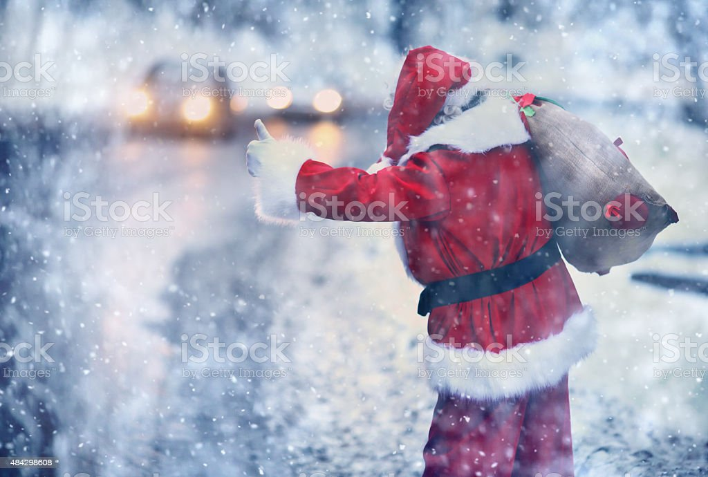 Santa Claus hitchhiking on a snowy day. stock photo