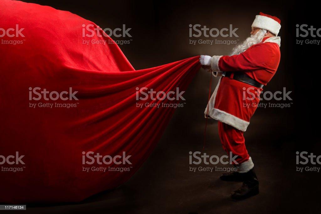Santa Claus holding a BIG gift bag royalty-free stock photo