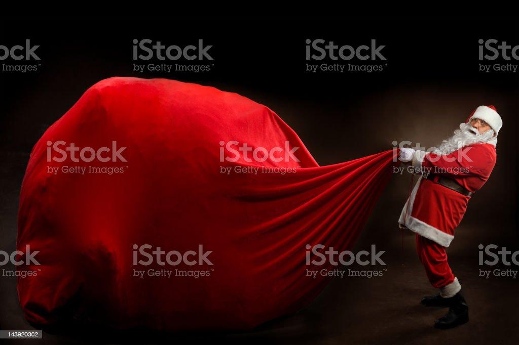 Santa Claus holding a BIG gift bag stock photo