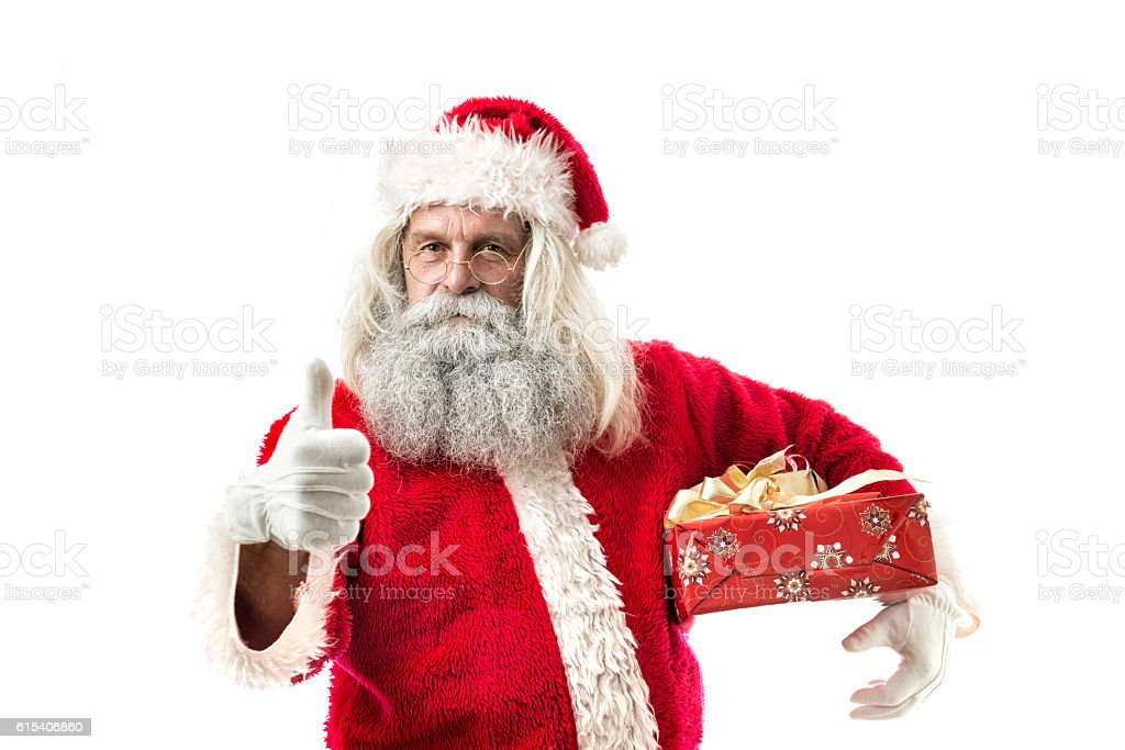 santa claus holding a present with thumb up stock photo