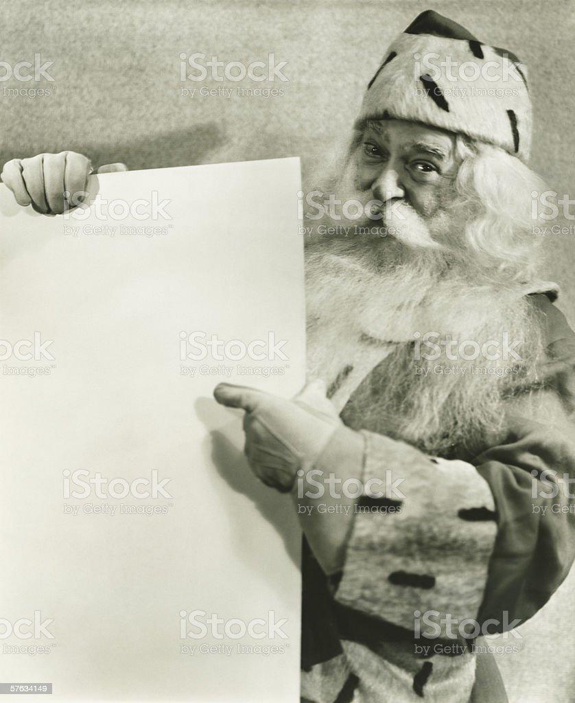 Santa Claus holding blank sheet of paper, (B&W), portrait royalty-free stock photo