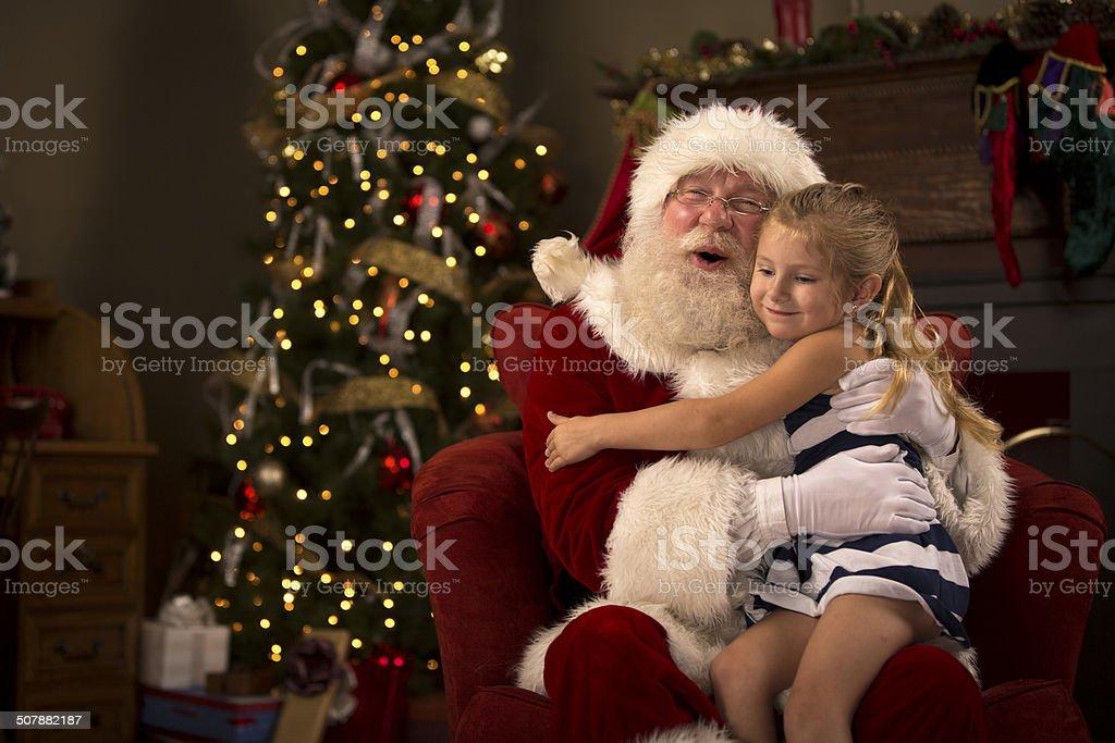 Santa Claus hugging a child stock photo