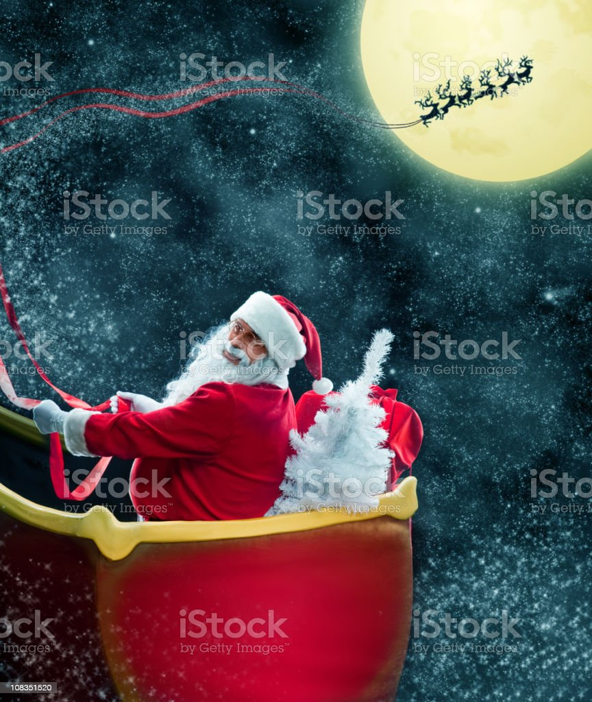 Santa Claus in his deer sled near the moon royalty-free stock photo
