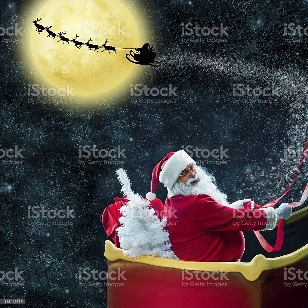 Santa Claus in his deer sled near the moon stock photo