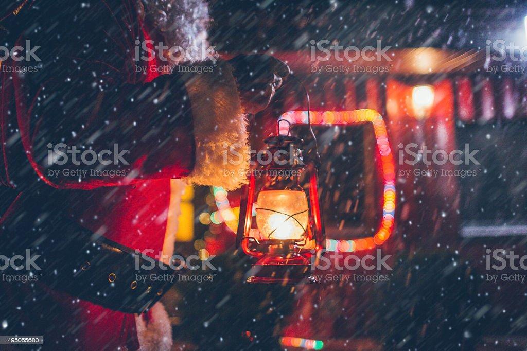 Santa Claus is lighting his way through a snowstorm stock photo