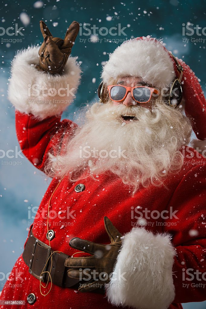 Santa Claus is listening to music in headphones outdoors stock photo