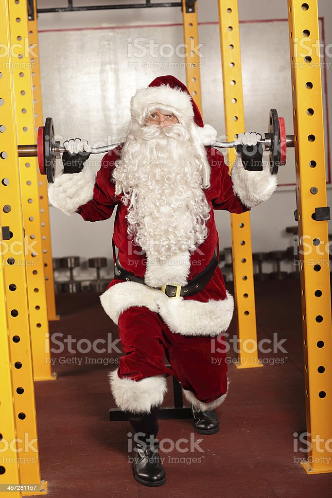 Santa Claus lifting weights in gym - training before Christmas stock photo