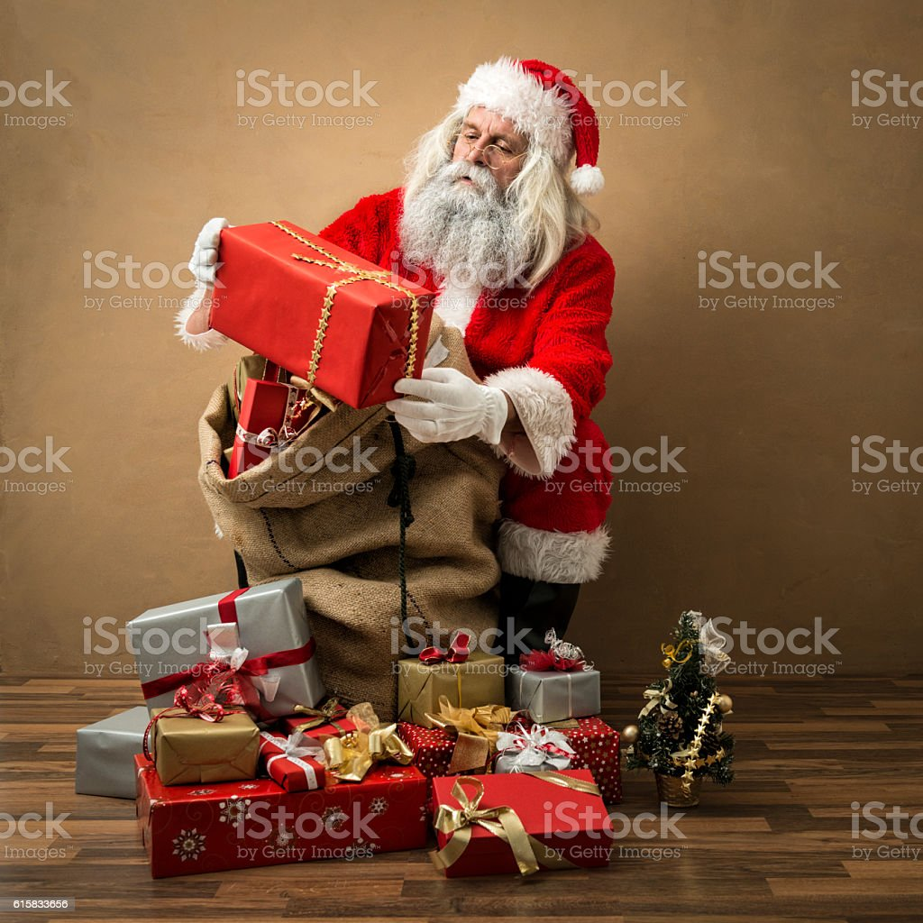 santa claus looking at present in his hands stock photo