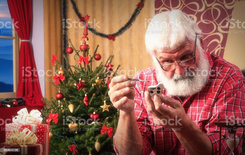 Santa Claus make presents for Christmas stock photo
