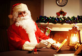 Santa Claus makes toy. Christmas decorations on wooden table