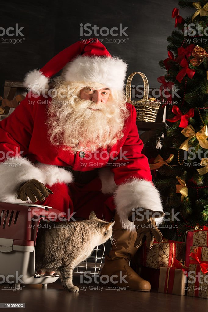 Santa Claus making a most wanted gift to a child stock photo