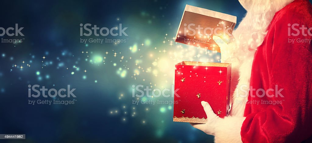 Santa Claus opening a red Christmas present stock photo