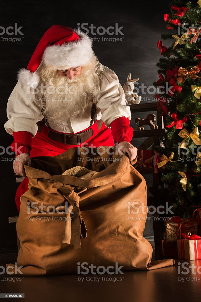 Santa Claus opening his sack and taking gifts stock photo