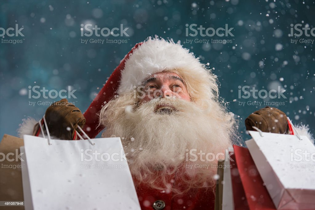 Santa Claus outdoors in snowfall holding shopping bags stock photo
