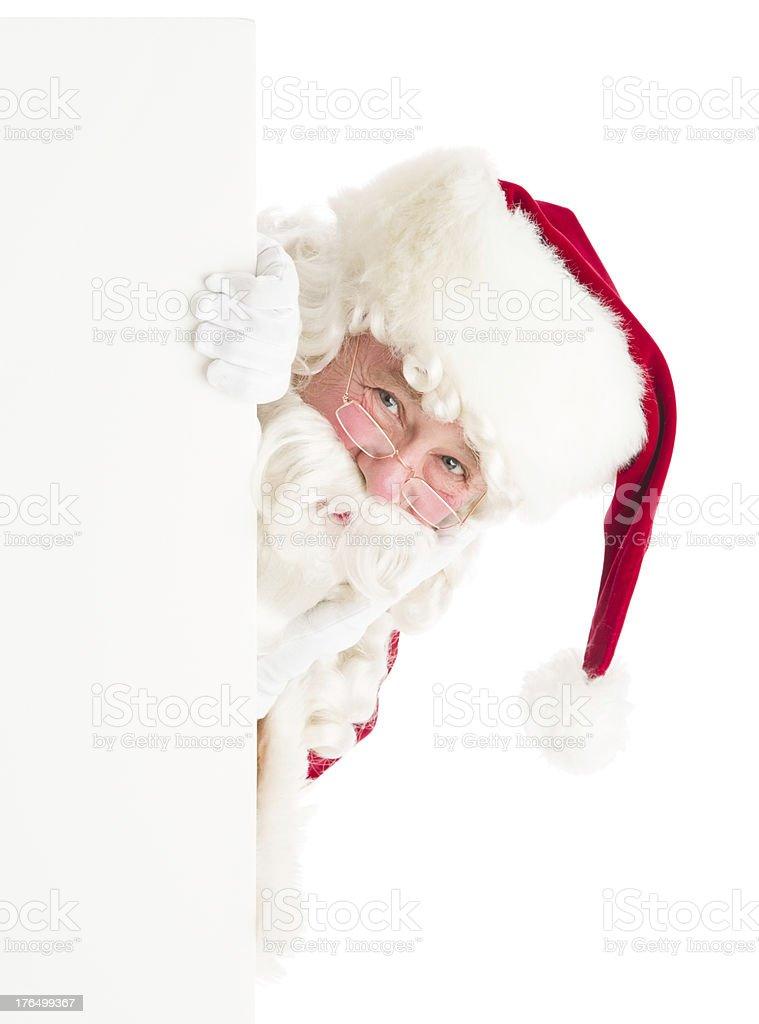 Santa Claus Peeking Through Blank Sign royalty-free stock photo
