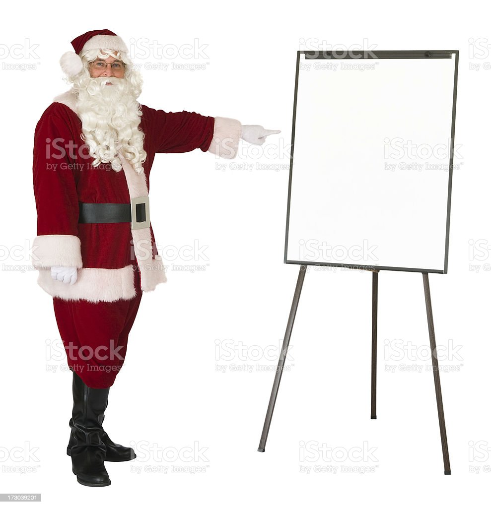 Santa Claus pointing to an isolated whiteboard royalty-free stock photo