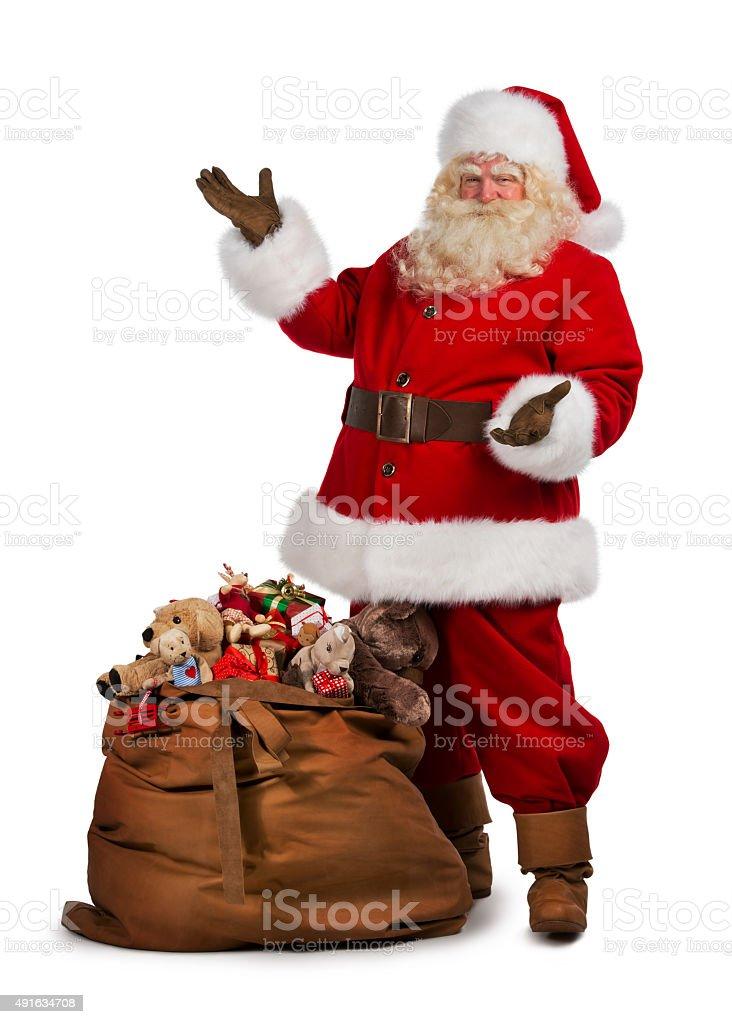 Santa Claus posing near a bag full of gifts stock photo