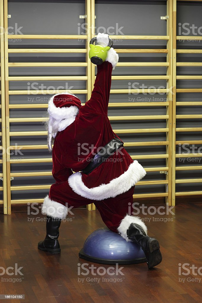 Santa Claus preparing for Christmas in gym - kettlebells training royalty-free stock photo