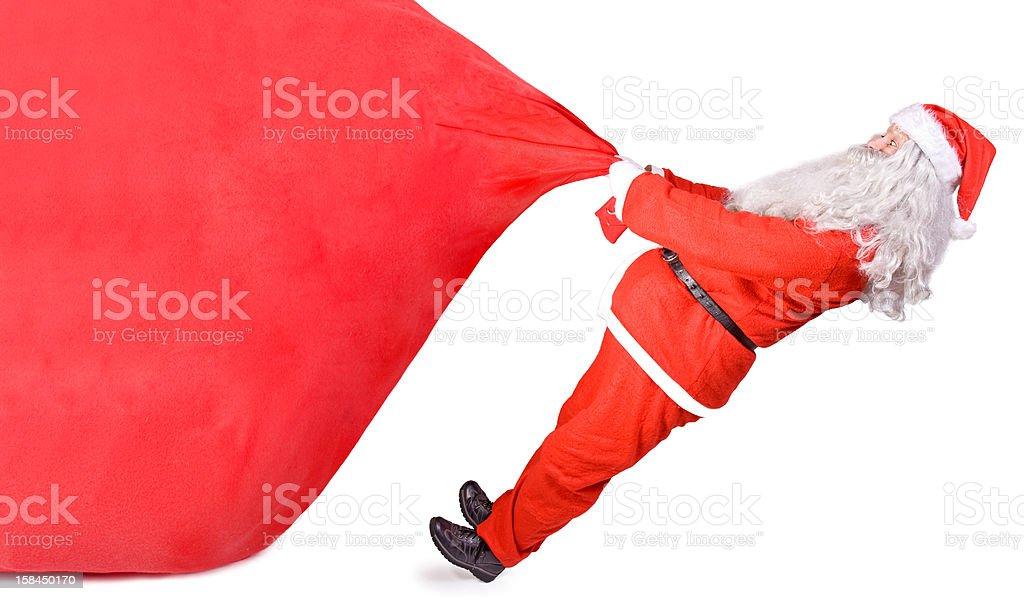 santa claus pulling a big bag stock photo