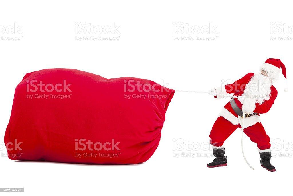 santa claus pulling a big gift  bag stock photo