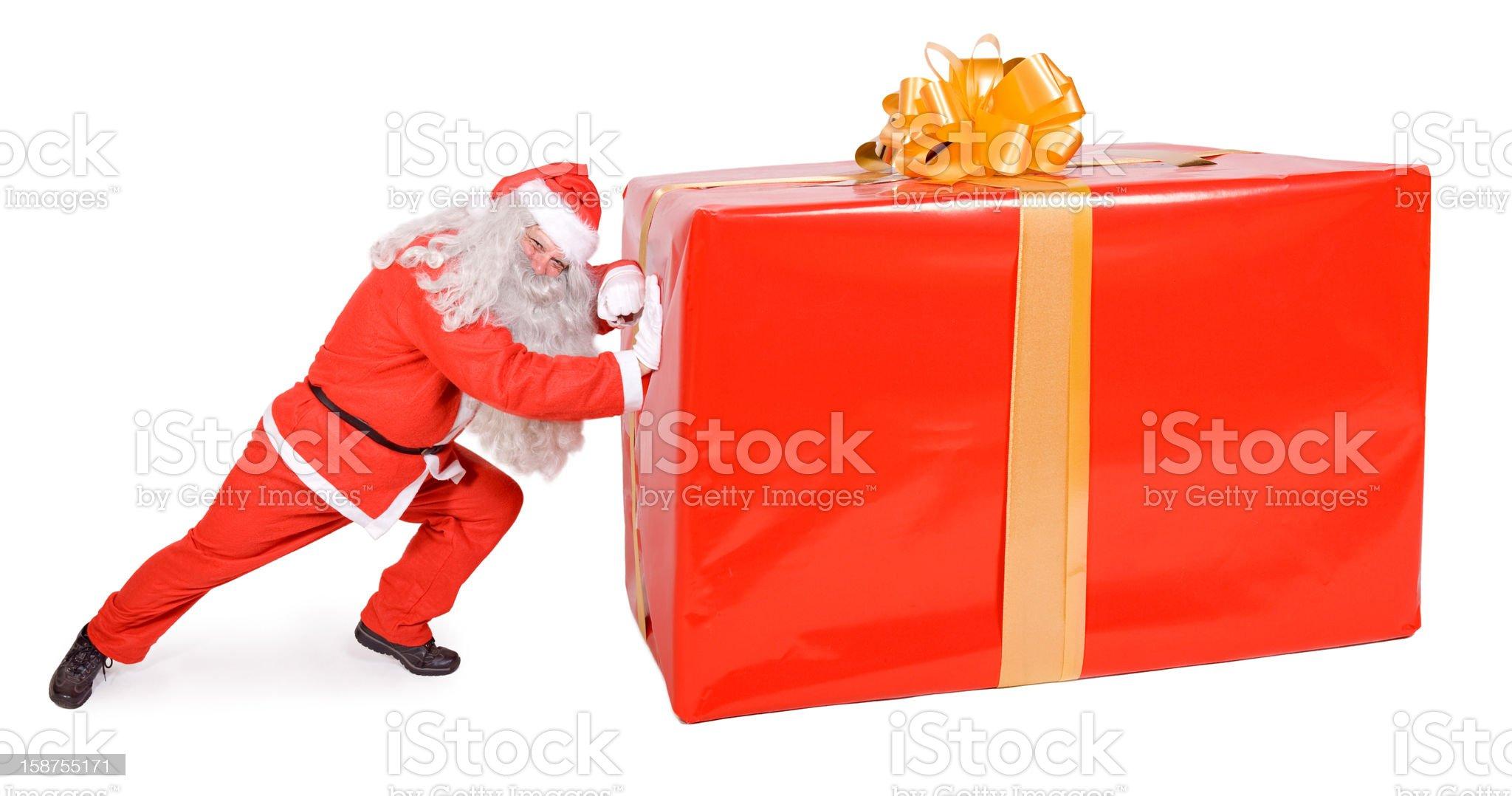 Santa Claus pushing a big gift royalty-free stock photo
