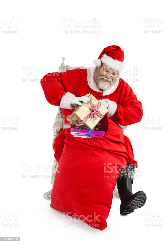 Santa claus putting presents in christmas bag stock photo