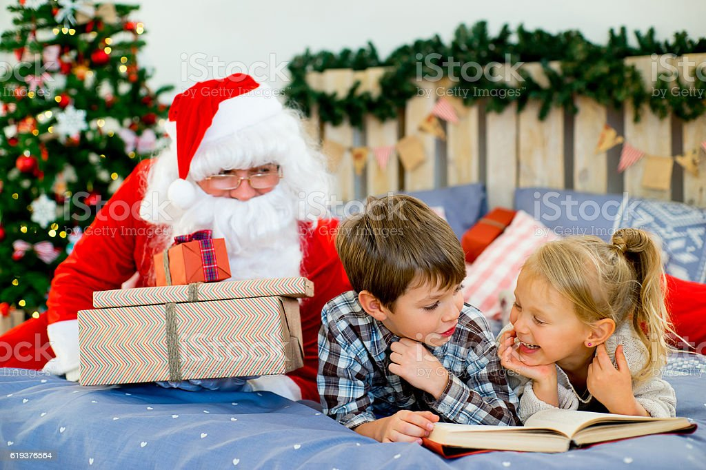 Santa Claus quietly came to the children who are reading stock photo