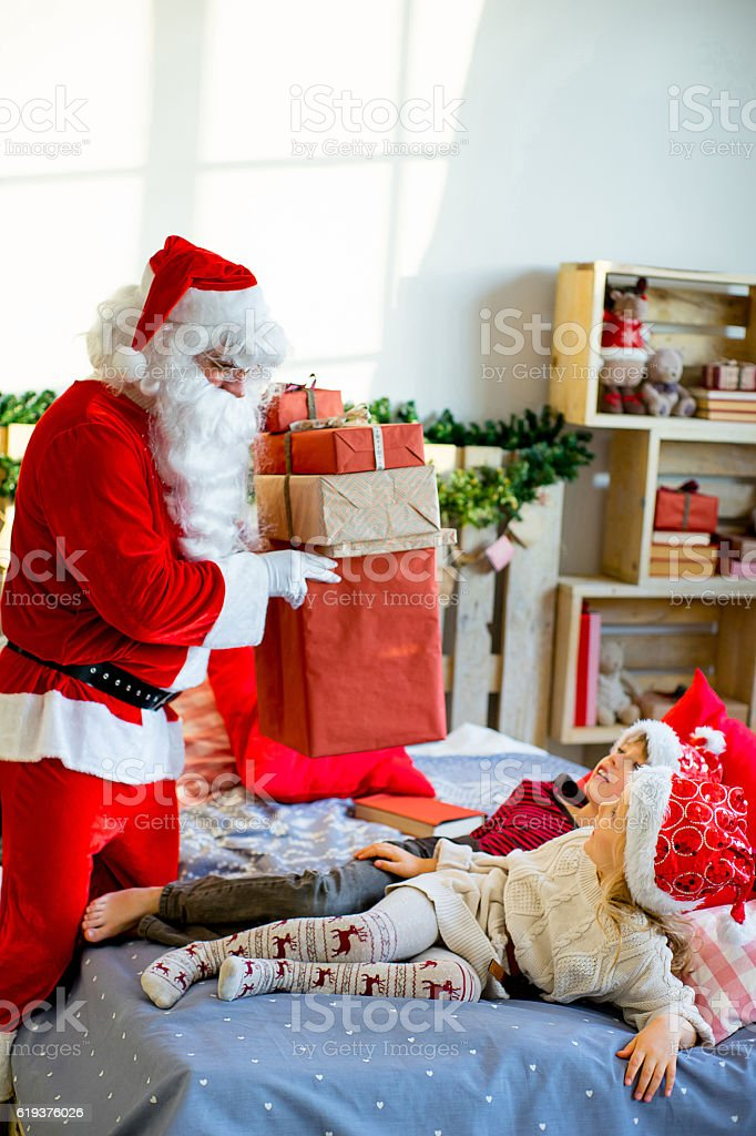 Santa Claus quietly came to the children who are sleeping stock photo