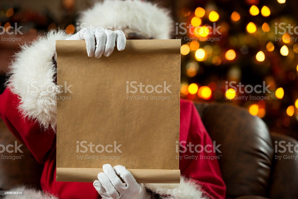 Santa Claus reading a wish list at home. stock photo