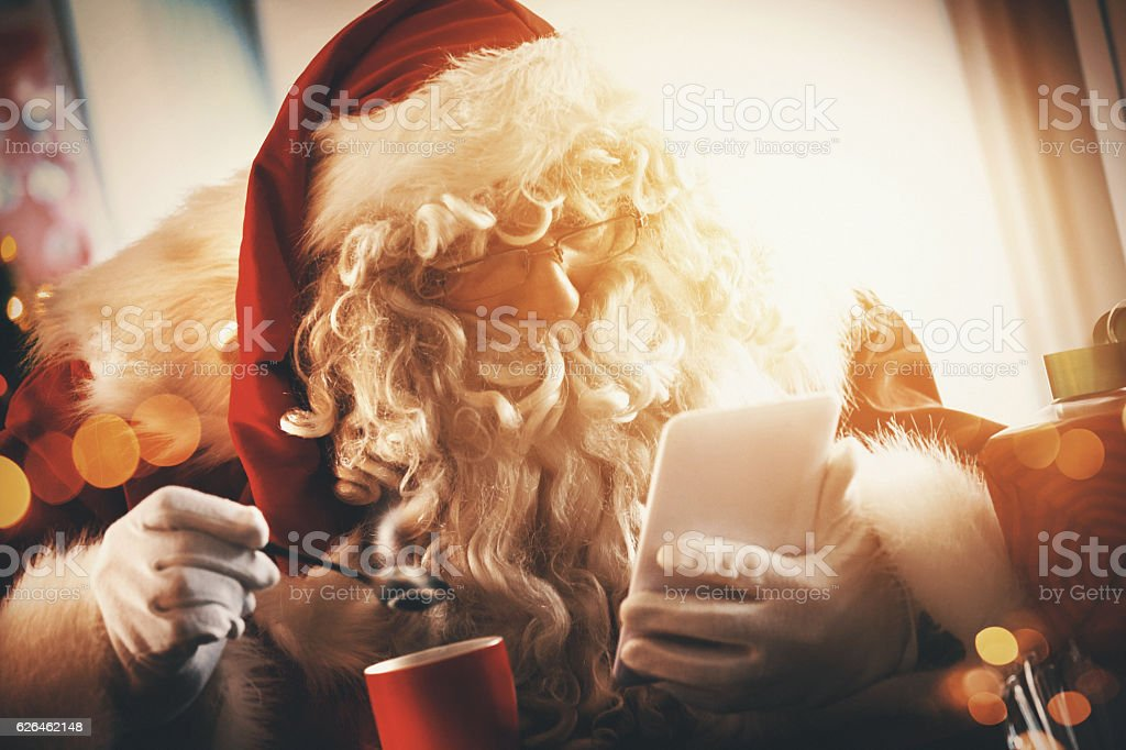 Santa Claus reading letters and wishlists. stock photo
