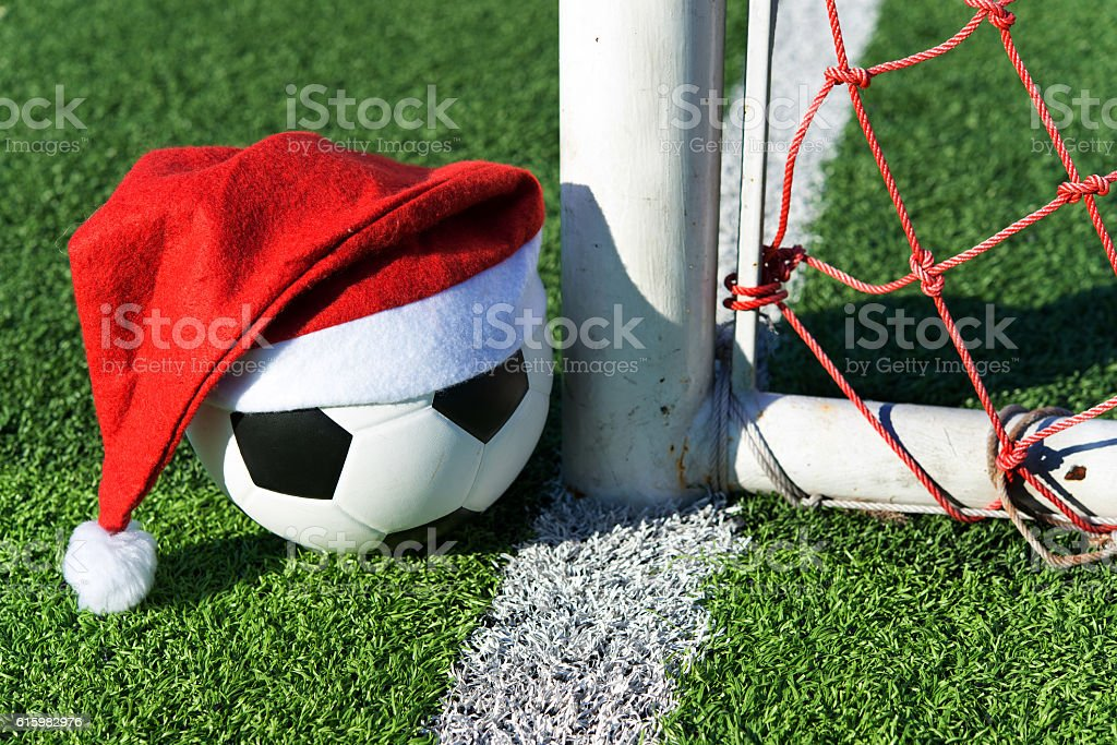santa claus red hat on soccer ball at green grass stock photo