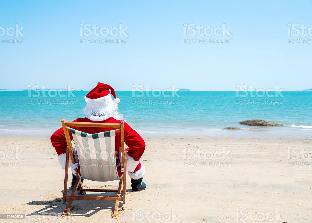 Santa claus relaxing on beach stock photo