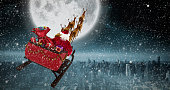 Santa Claus riding on sled against balcony overlooking city