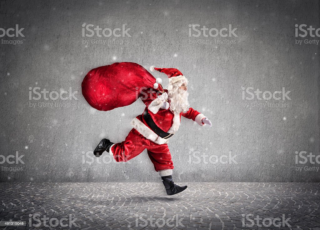 Santa Claus Running With A bag Of Gifts On Way stock photo