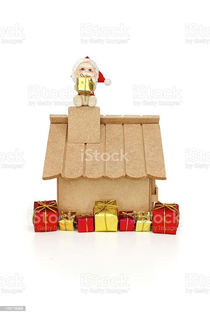 Santa Claus seating on chimney holding a gift royalty-free stock photo
